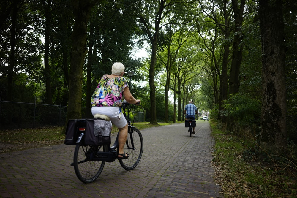 two person riding bicycle on brick roads during daytime