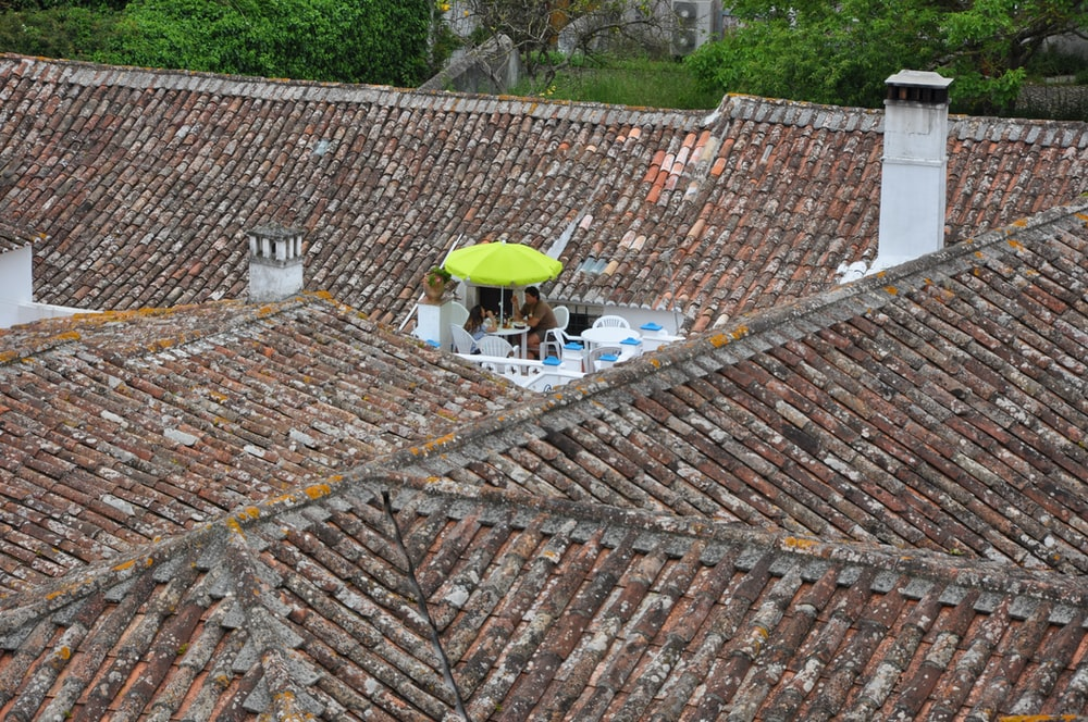 man sitting on chair on rooftop with umbrella during daytime