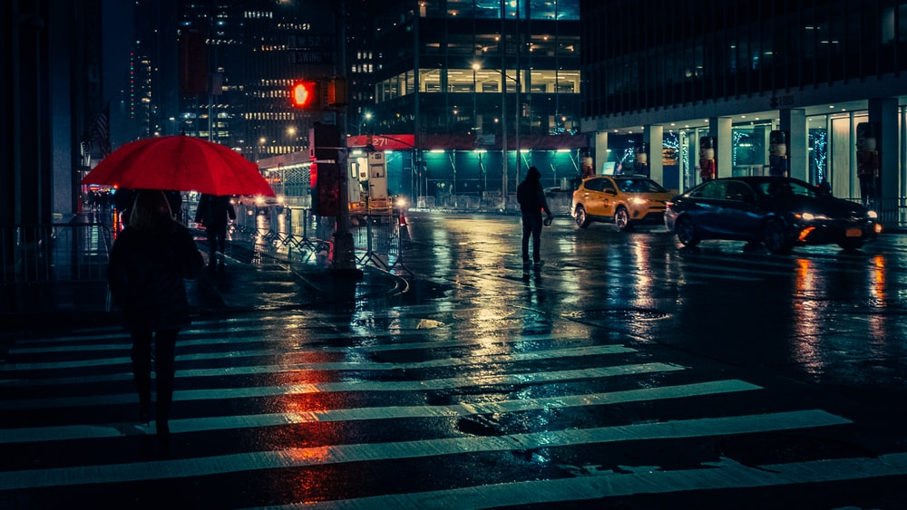 person carrying red umbrella passing on pedestrian lane