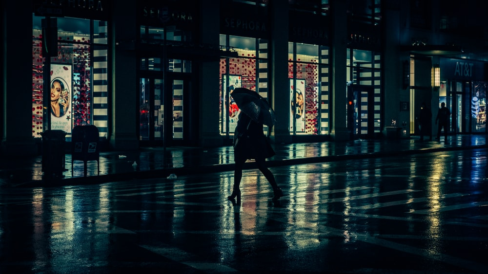 person with umbrella walking beside building during nighttime