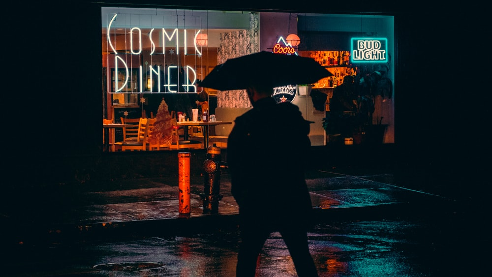 man under umbrella walking toward COsmic Diner building