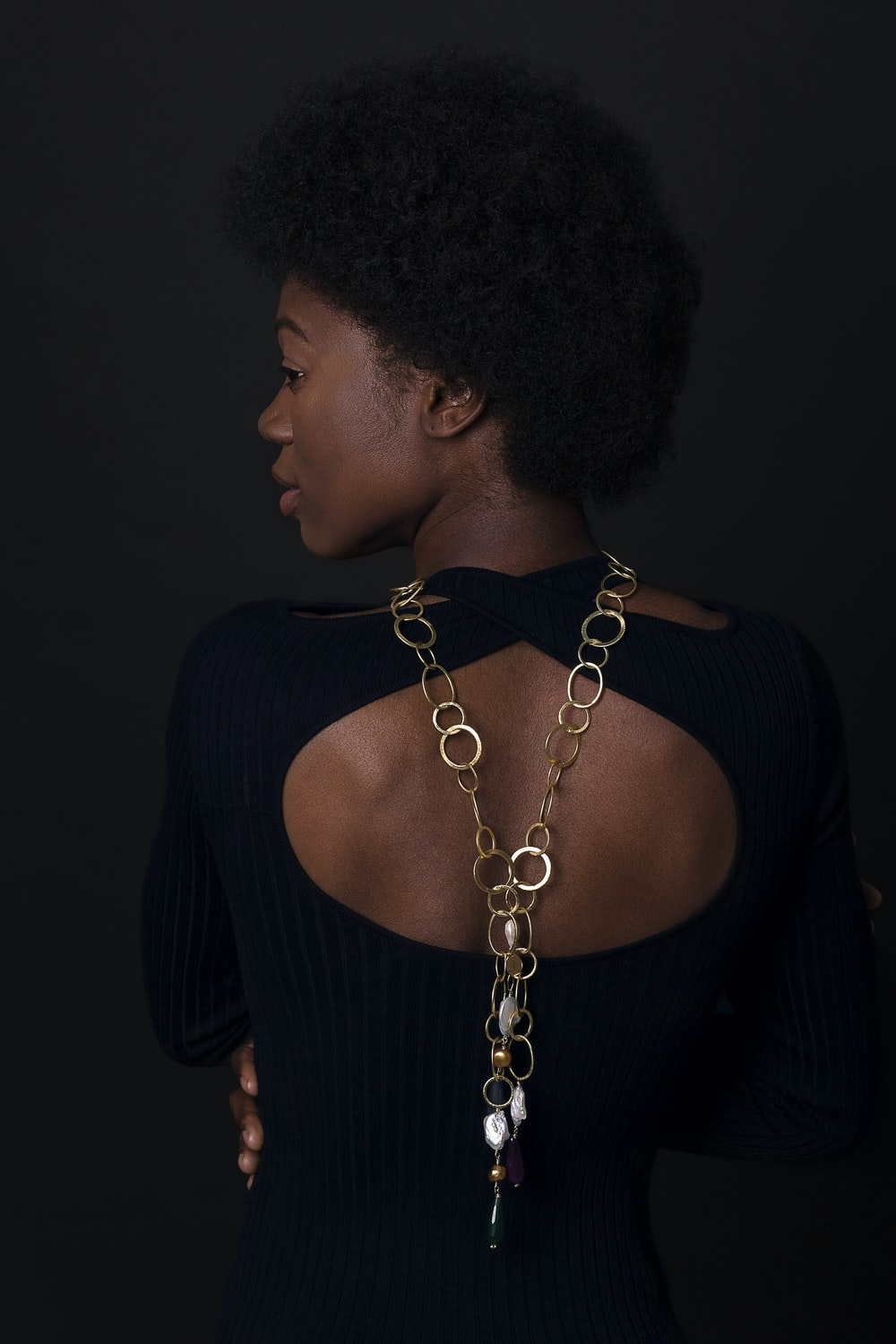 woman in black dress with silver-colored necklace
