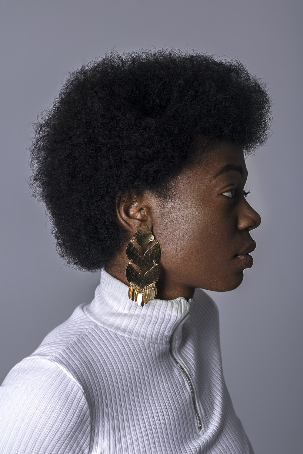woman wearing white turtleneck top and gold-colored earring