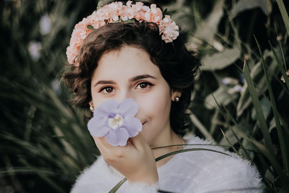 woman smelling purple flower