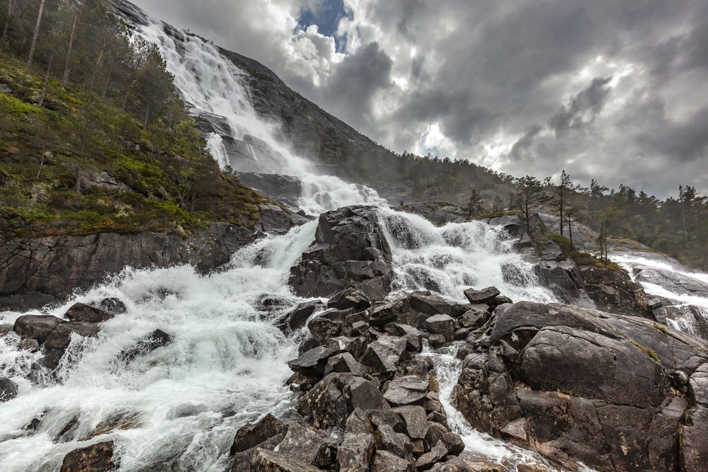 water falls splashing on rocks during daytime