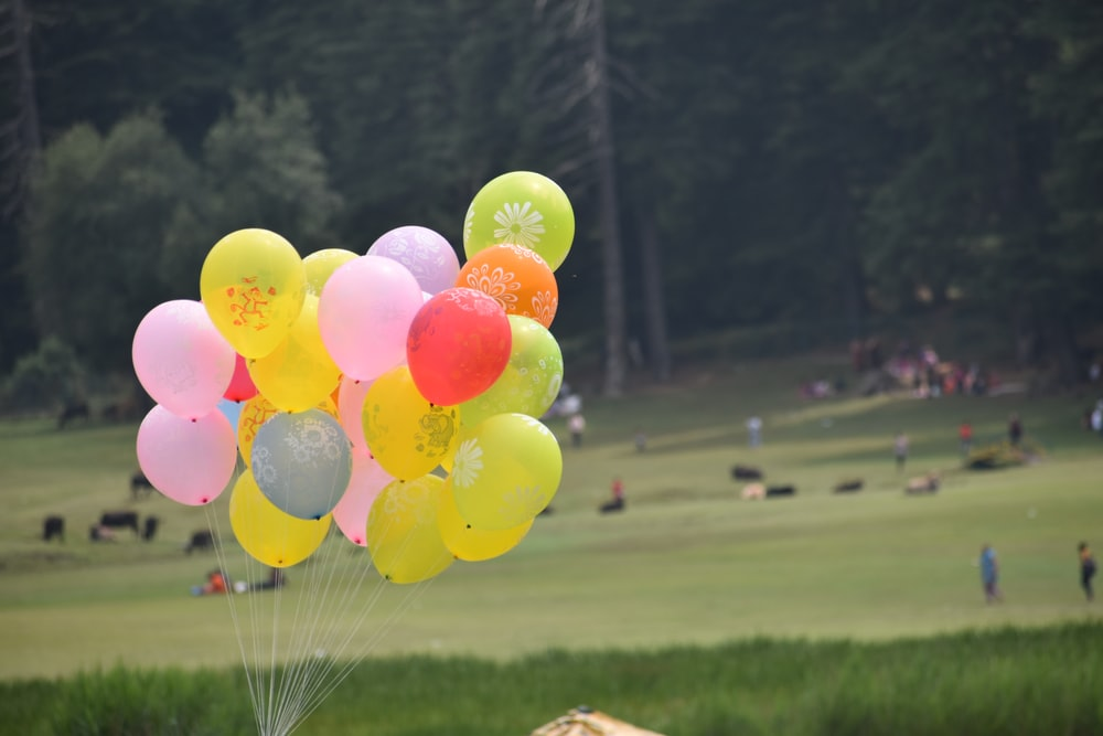 pink and yellow latex balloons on mid air