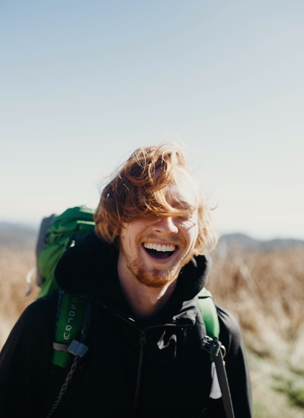 smiling man with green mountaineering bag during daytime