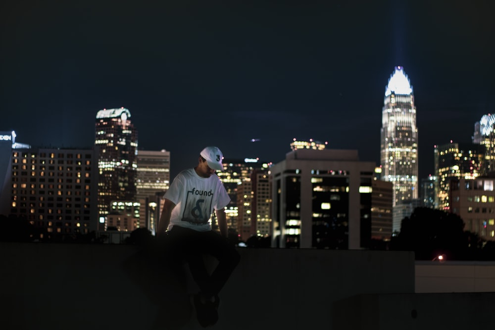 man sitting on pavement with buildings during night time