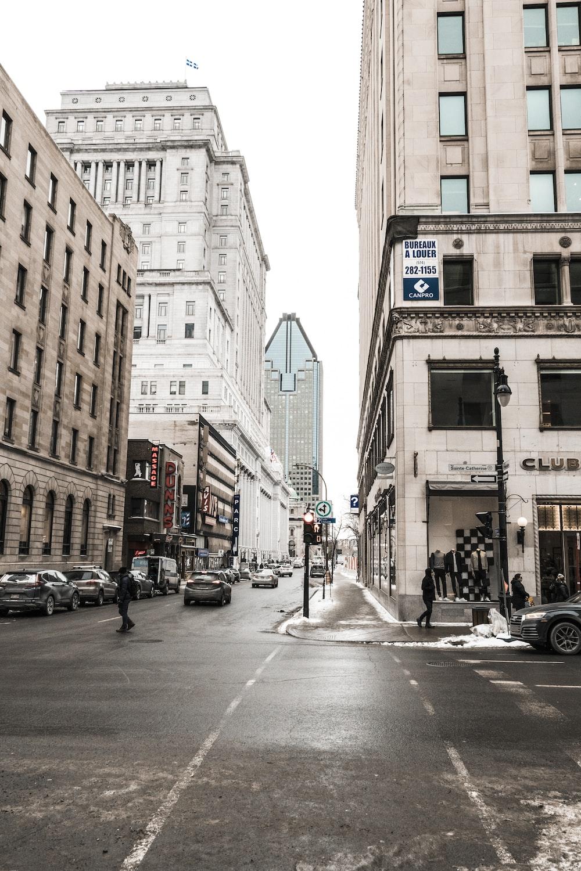 people walking on street with vehicle park beside buildings