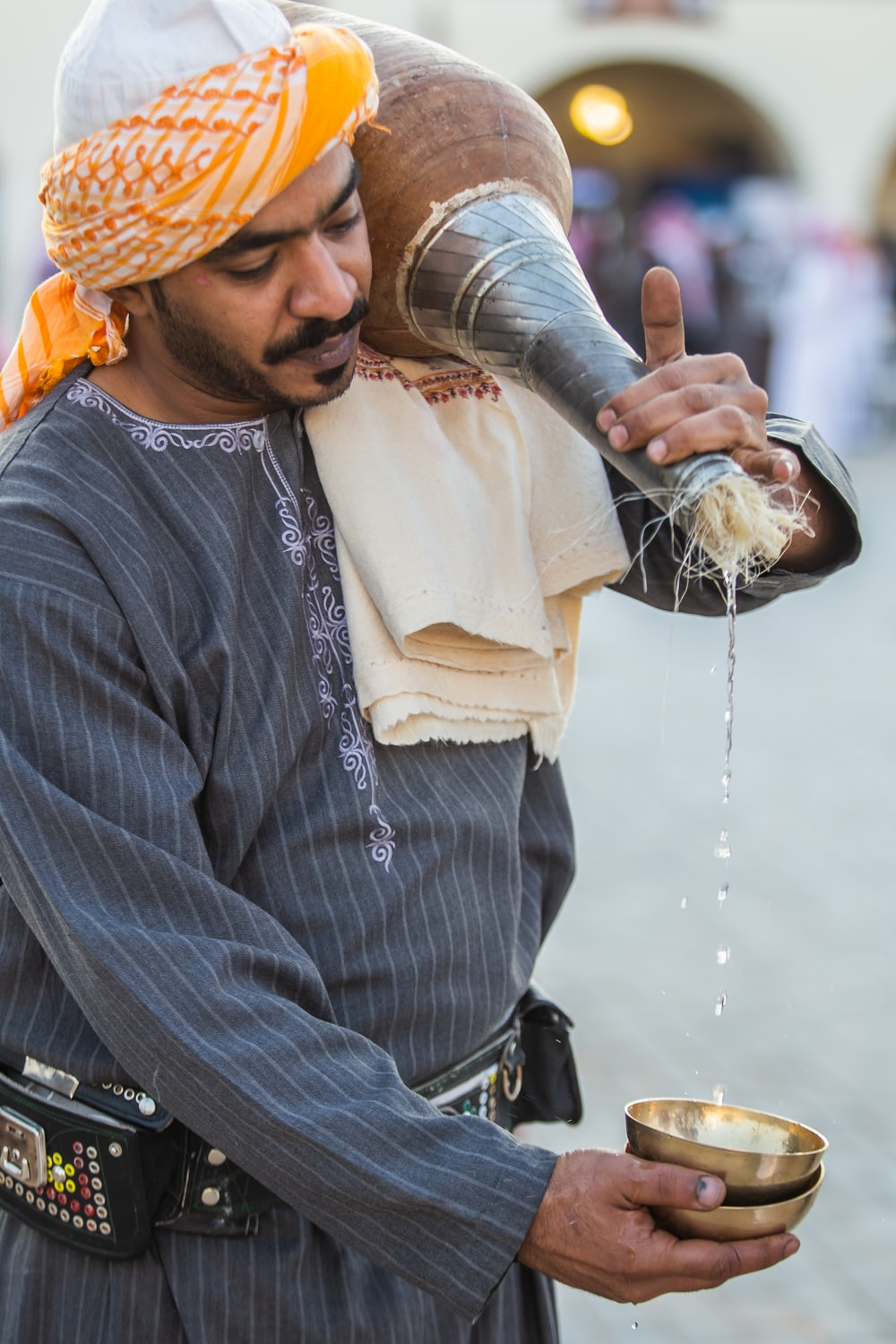 man in grey shirt pouring liquid on brass cup from container on his shoulder