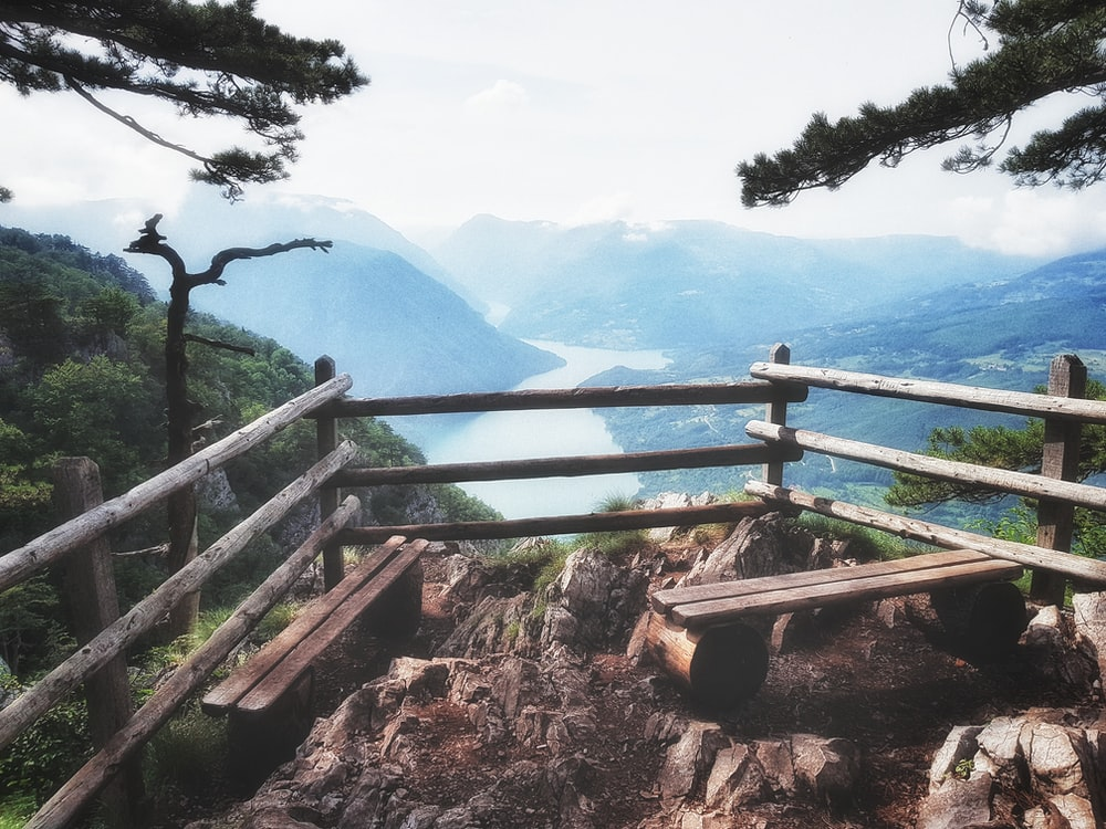 brown wooden bench on top of mountain near river