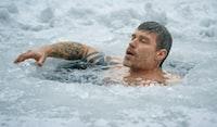 man swimming on frozen water