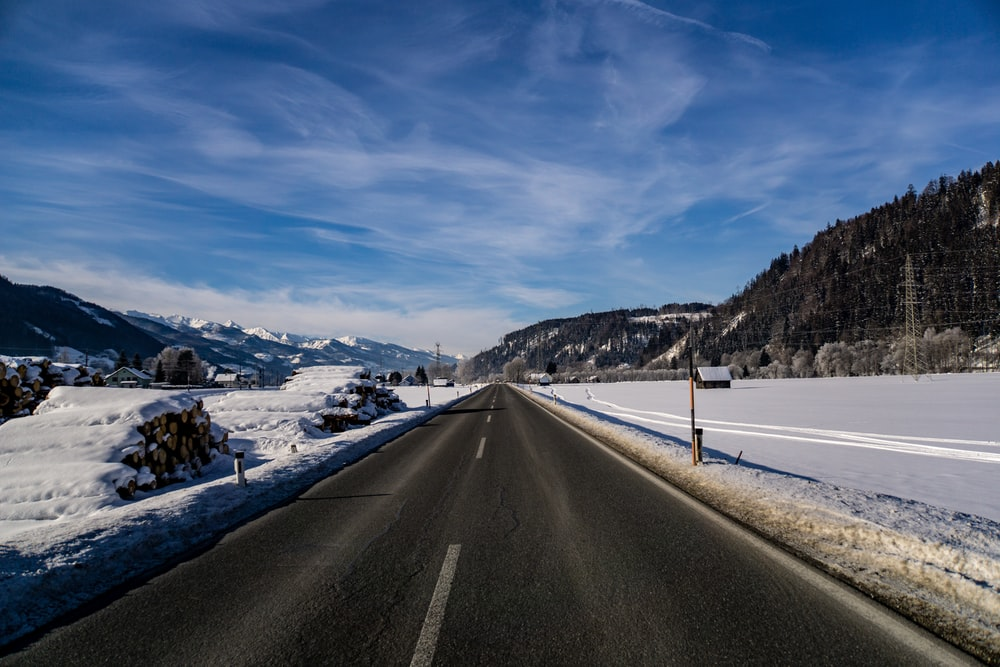 asphalt road between snow covered roads on daylight