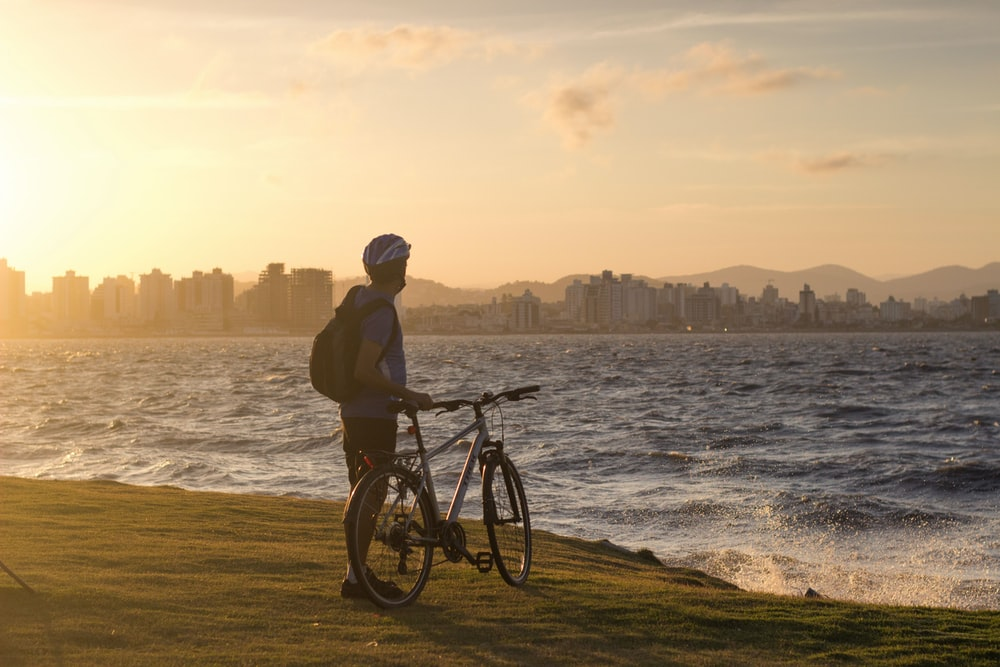 man wearing bike helmet standing on shore with bike