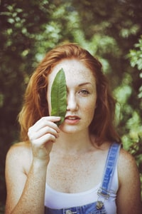 woman in blue denim jumper holding linear leaf on her right eye