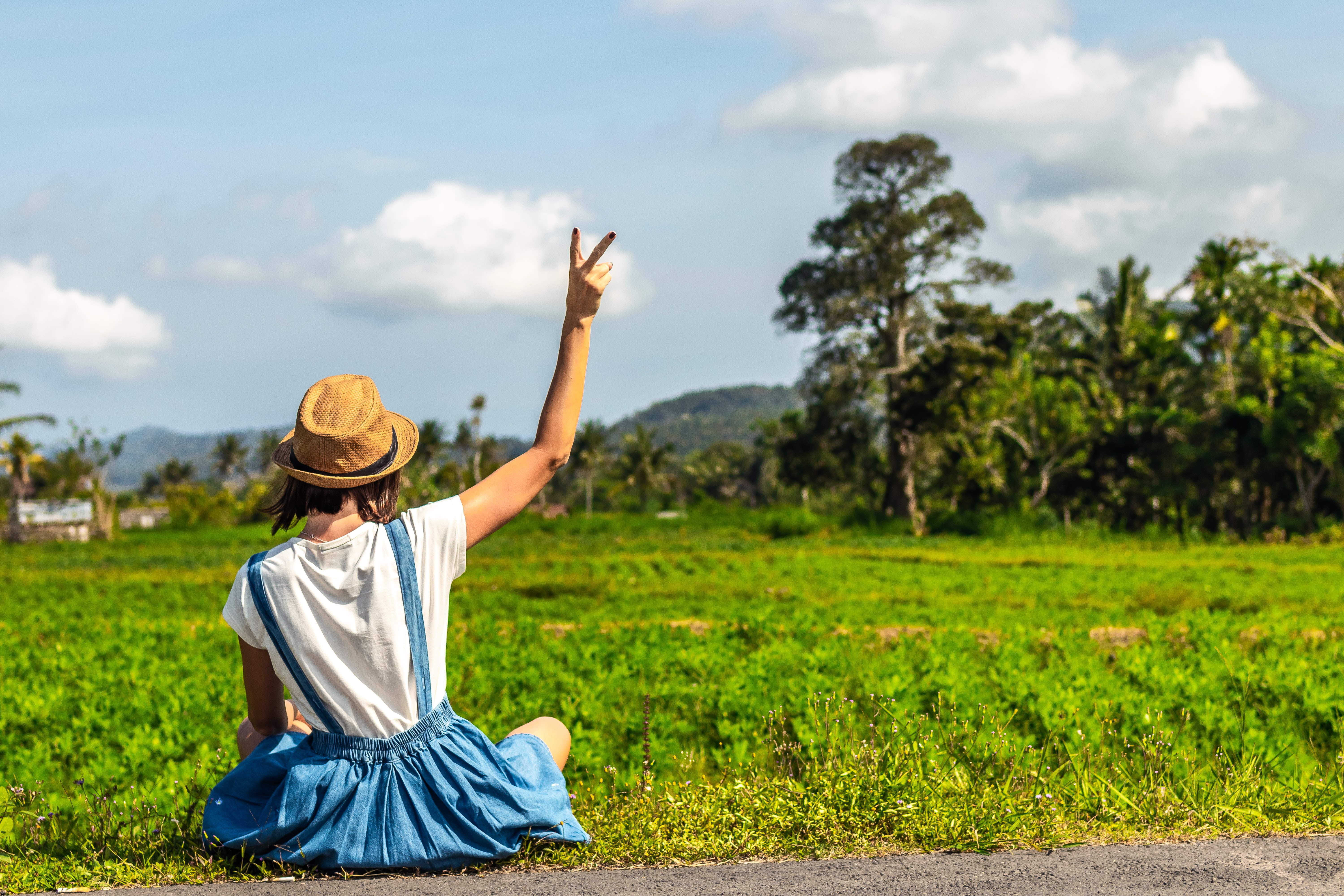 woman sitting on green grass while making peace sign post