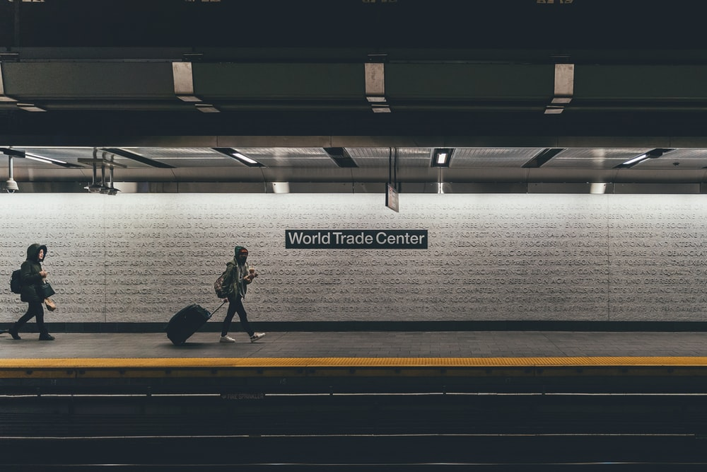 person with rolling bag walking on the side of the rail with World Trade Center signage