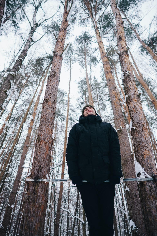man in black jacket doing exercise near trees