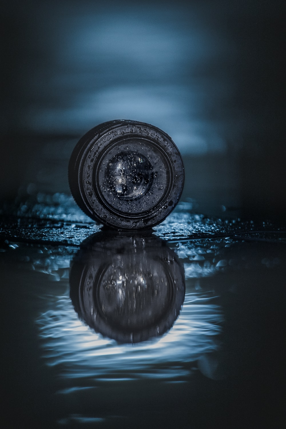 round black smartphone lens with reflection on water digital wallpaper