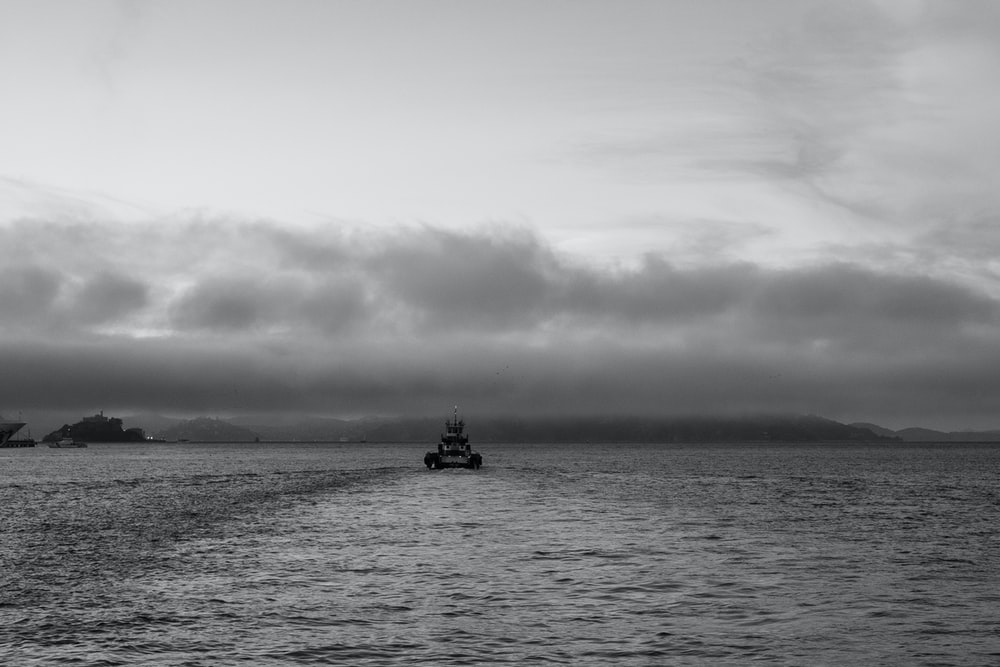 grayscale photo of boat on ocean