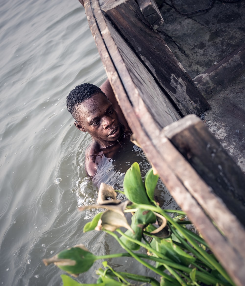 man in body of water holding on side of boat
