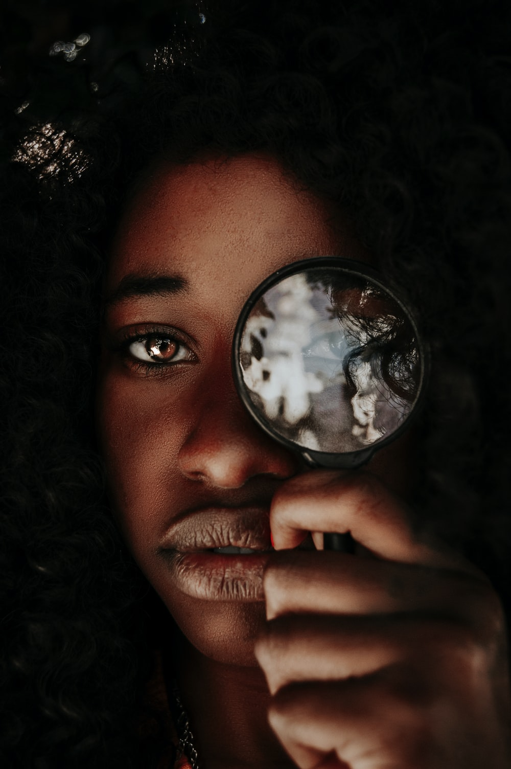 woman placing magnifier on her left eye