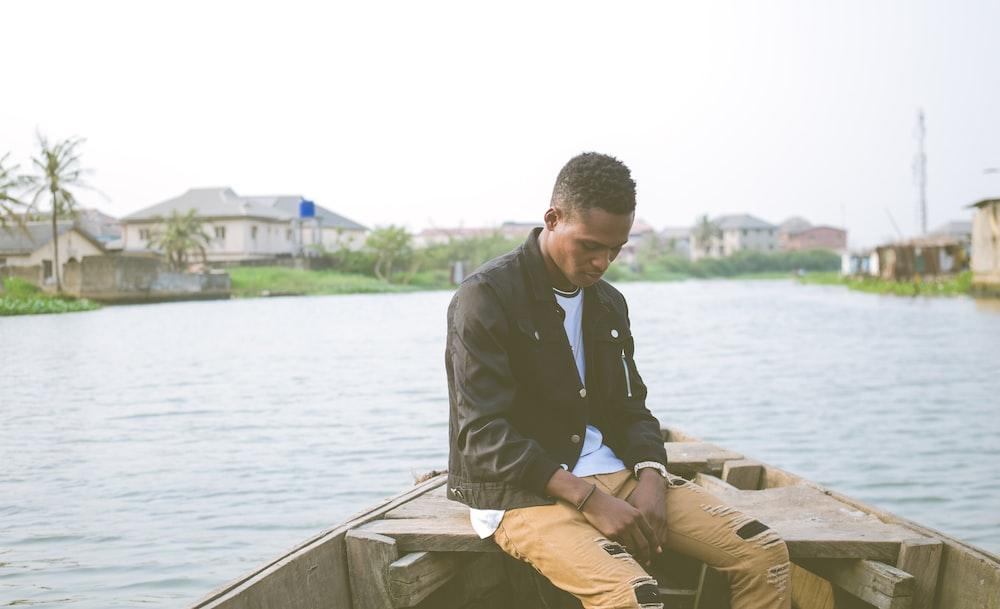 man wearing black jacket sitting on boat
