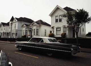 black car near white house