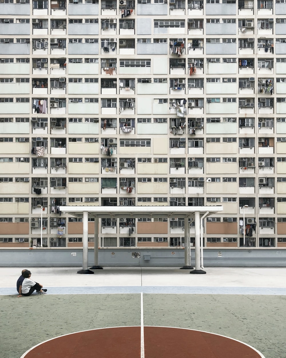 two people sitting on concrete pavement in front of high-rise building
