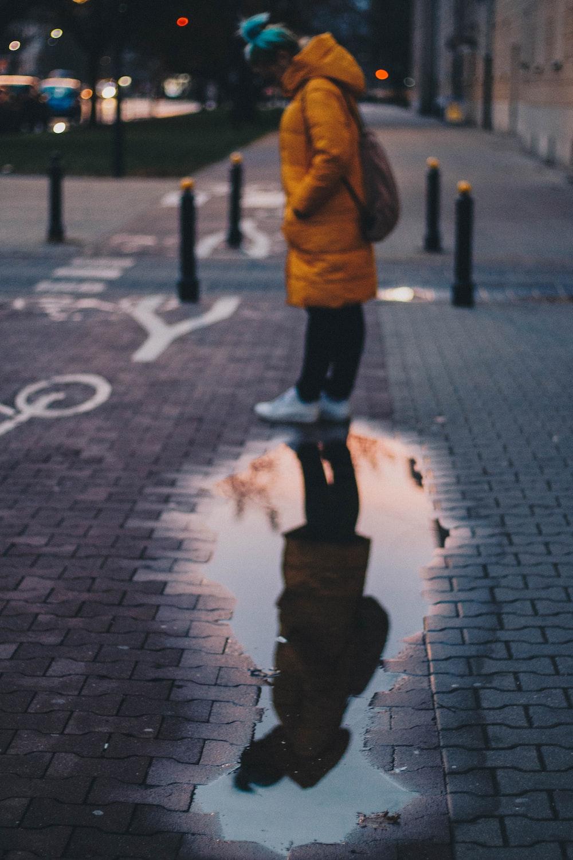 woman standing beside wet road
