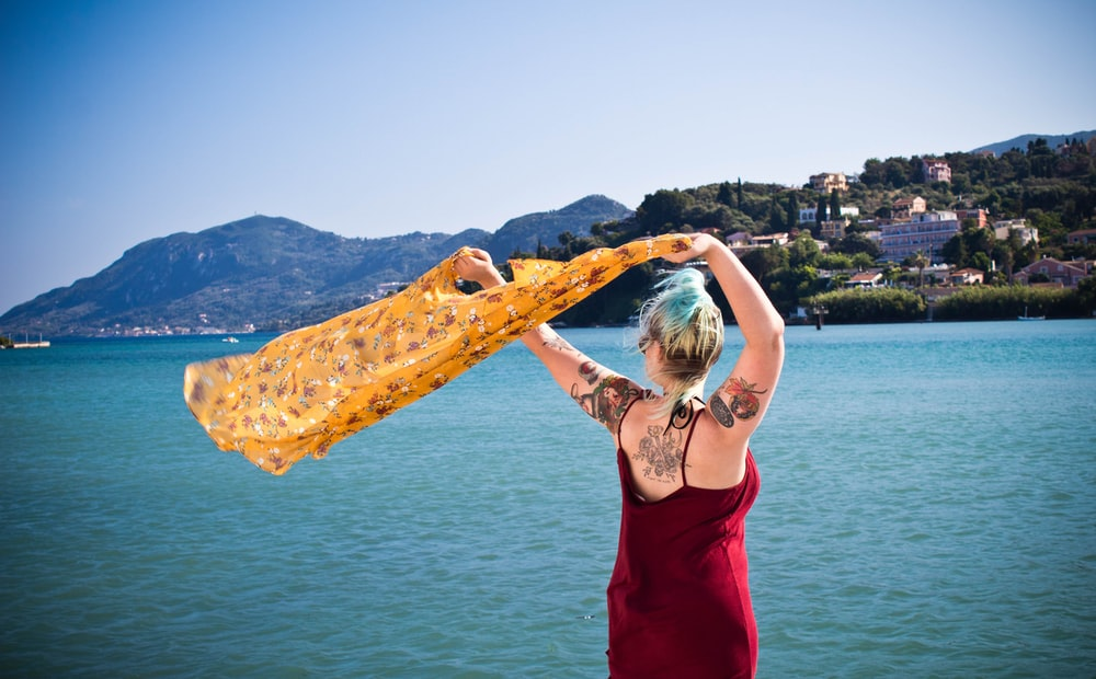 woman waving yellow textile near body of water during daytime