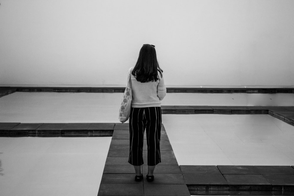 grayscale photography of woman standing beside body of water