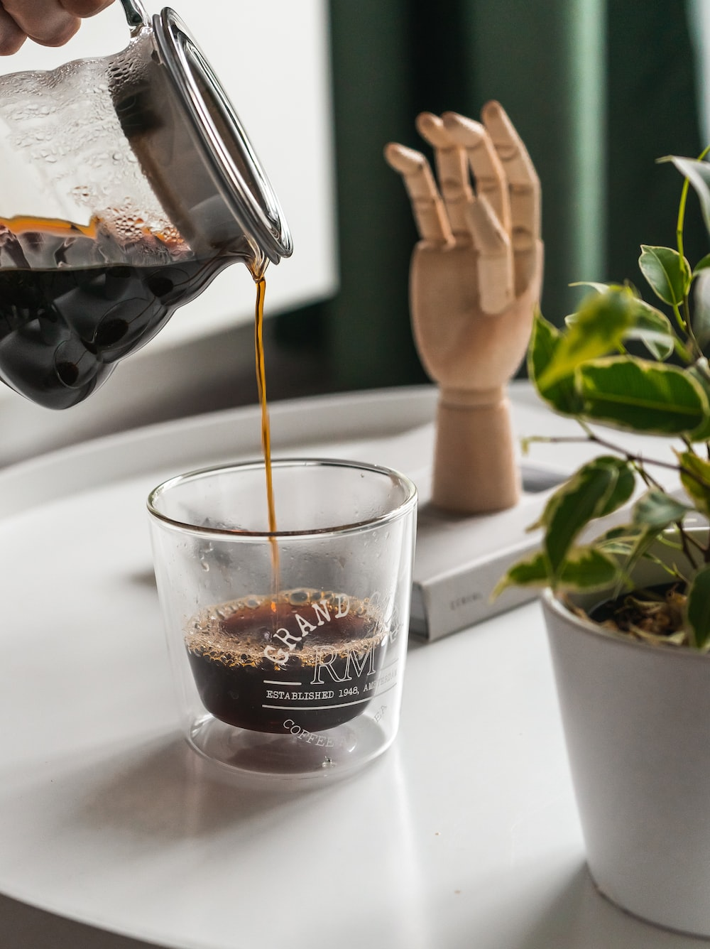 selective focus photo of person pouring coffee on clear drinking glass