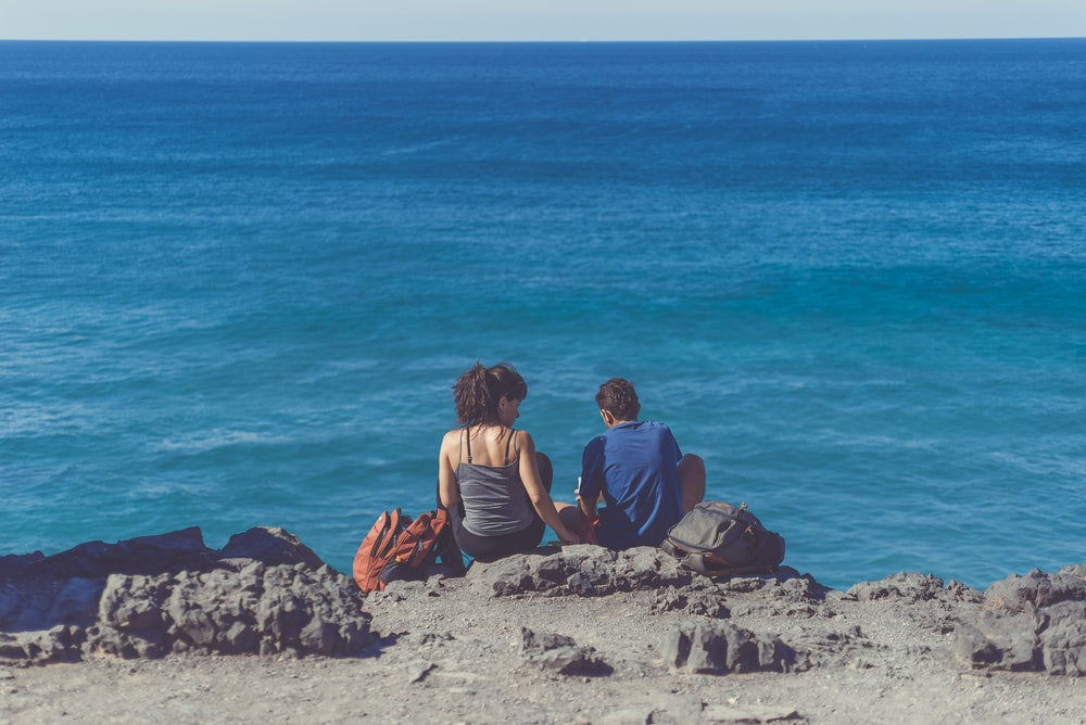 man and woman sitting next to each other on cliff in front of body of water