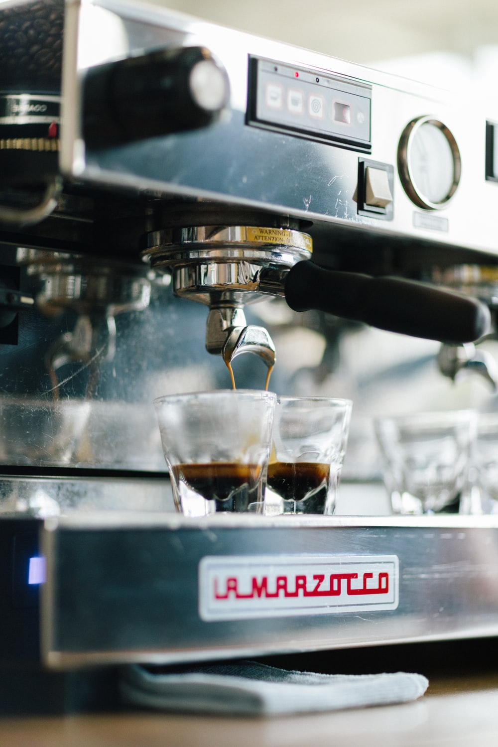 selective focus photography of black and gray espresso making machine