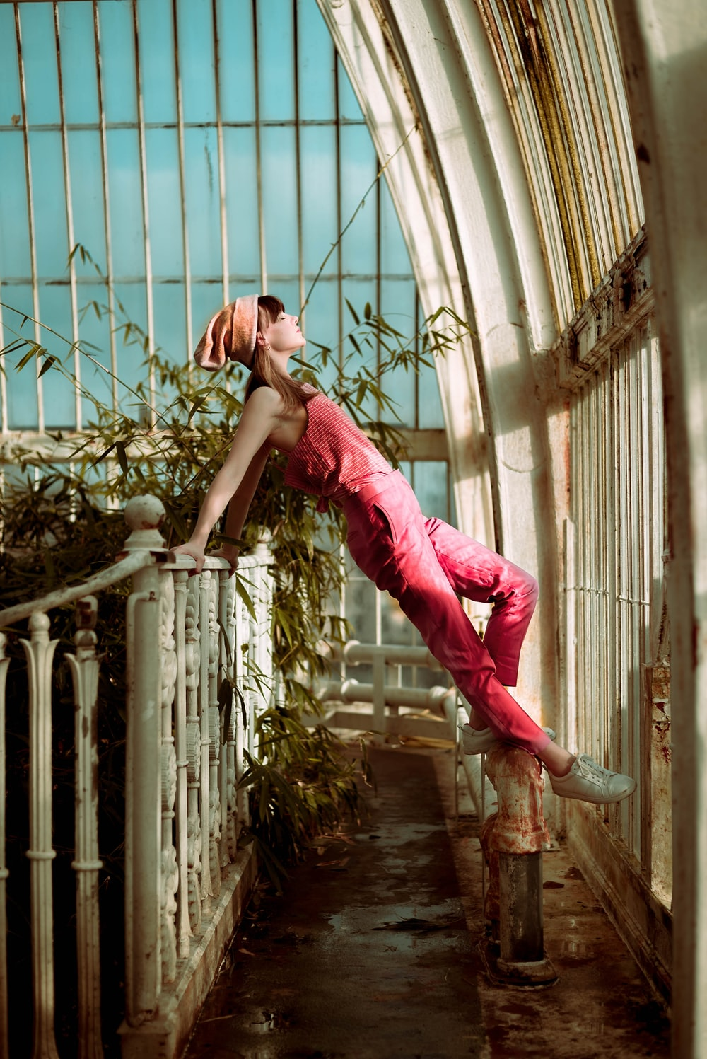 woman wearing pink overalls with feet on white pedestal while her hands holding on metal rail