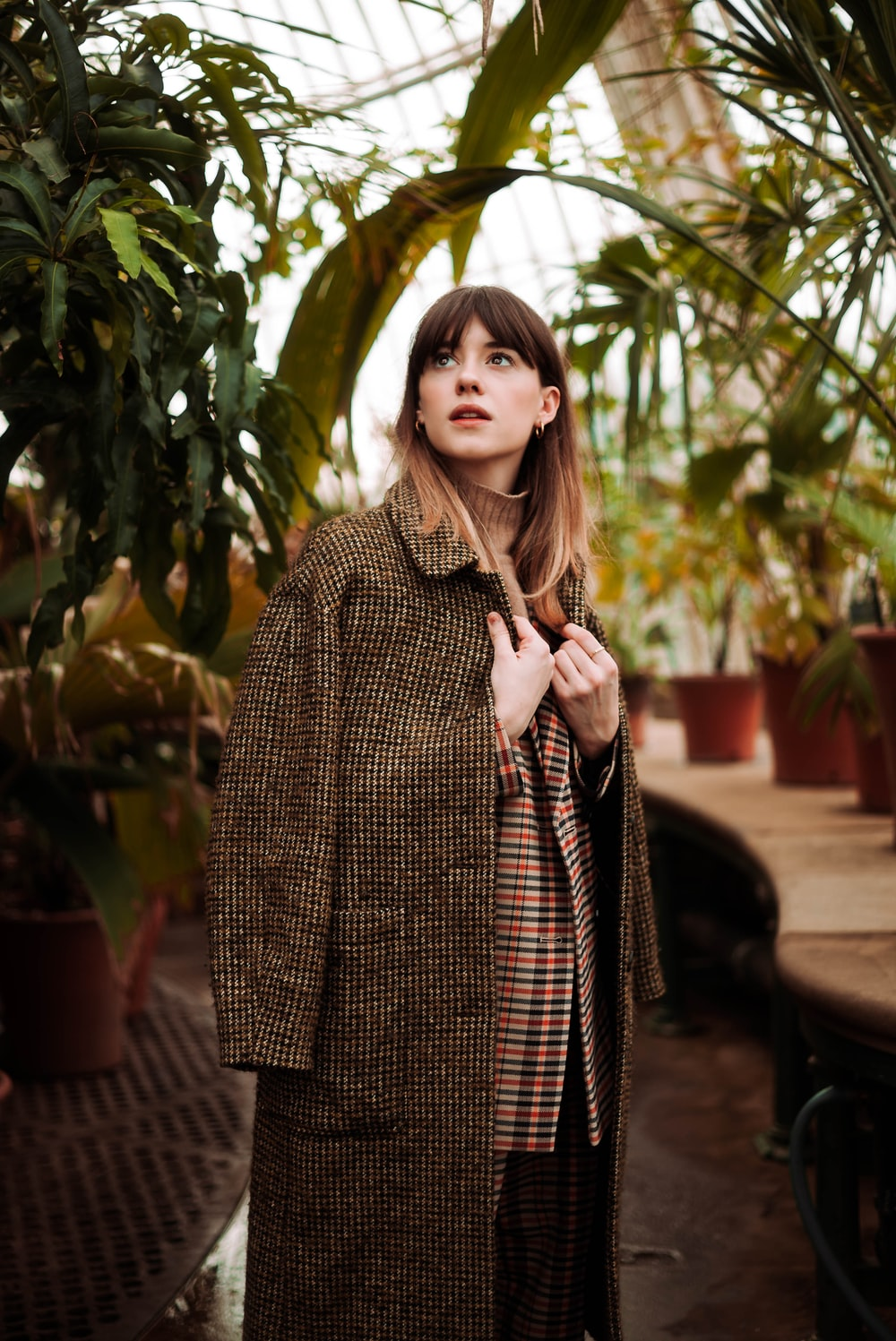 woman wearing brown coat near plants