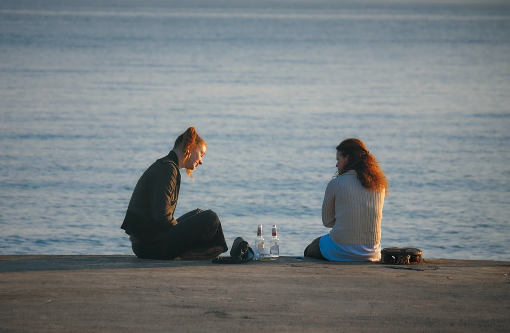 2 women sitting on concrete with bottles in between them during daytime