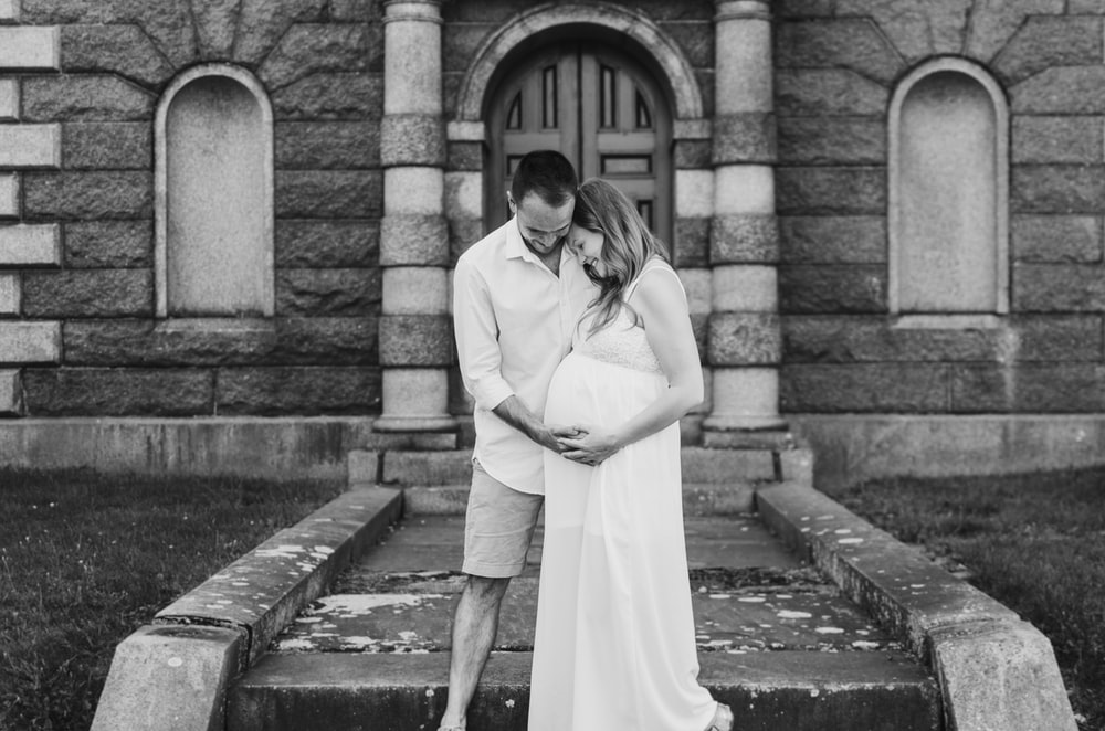 grayscale photography of man touching woman's pregnant belly