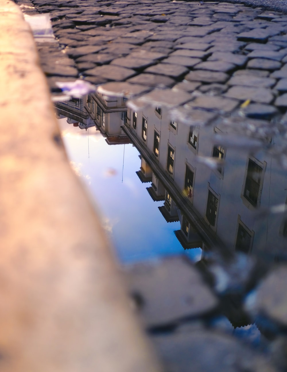 gray concrete building reflecting on road puddle