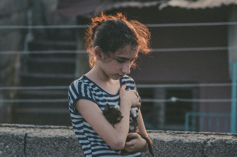 selective focus photo of woman holding puppy near gray wall
