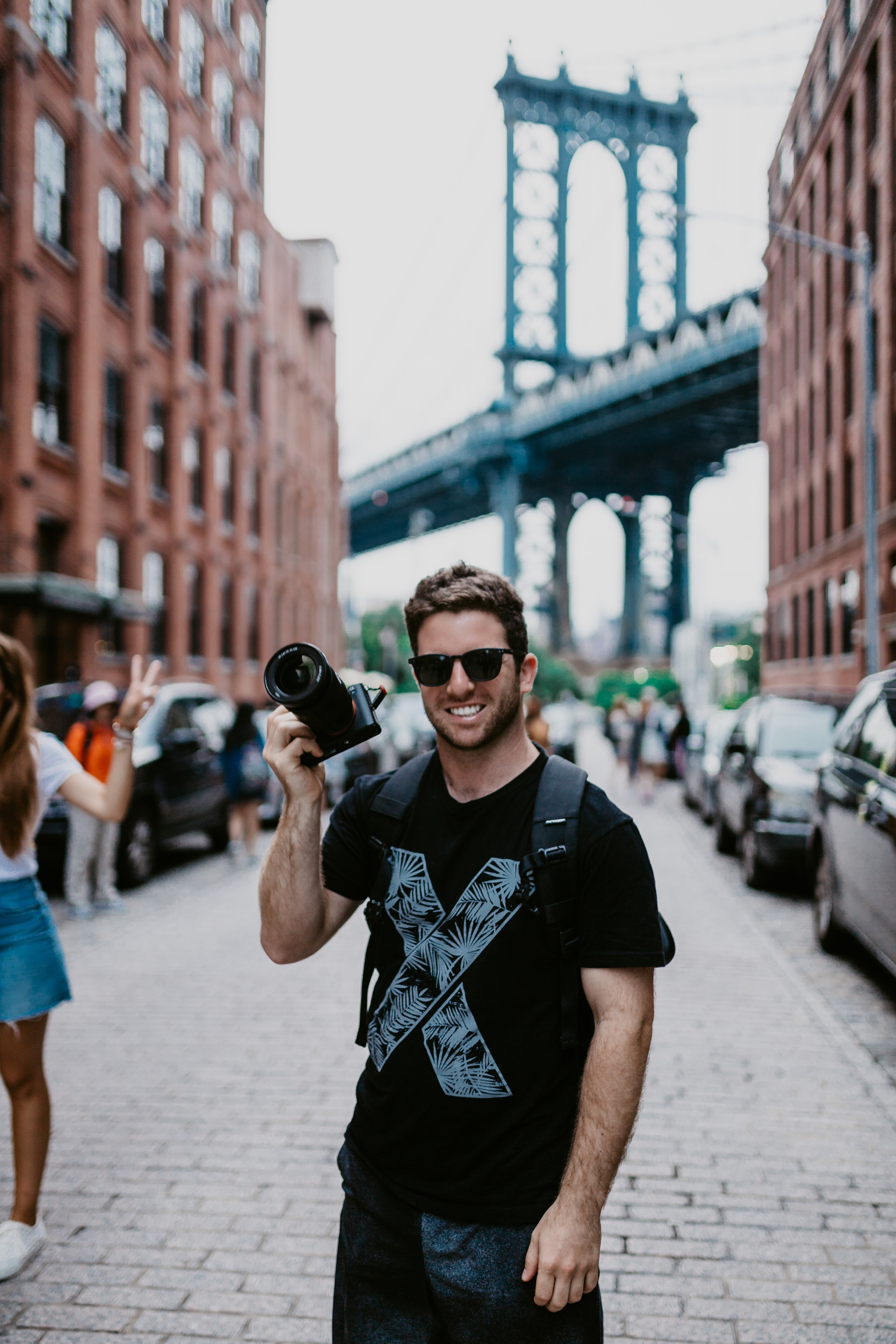 smiling man holding DSLR camera carrying backpack near parked cars during daytimes
