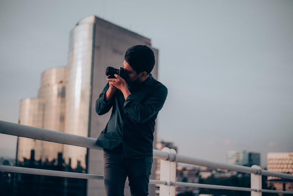 man in black shirt using DSLR camera