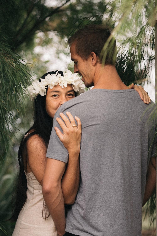 selective focus photography of woman embracing man