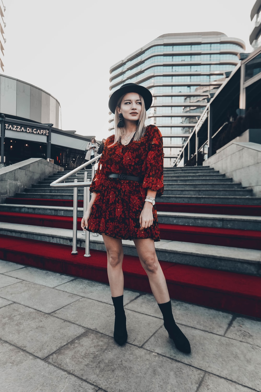 woman in red and black floral dress standing near stairs