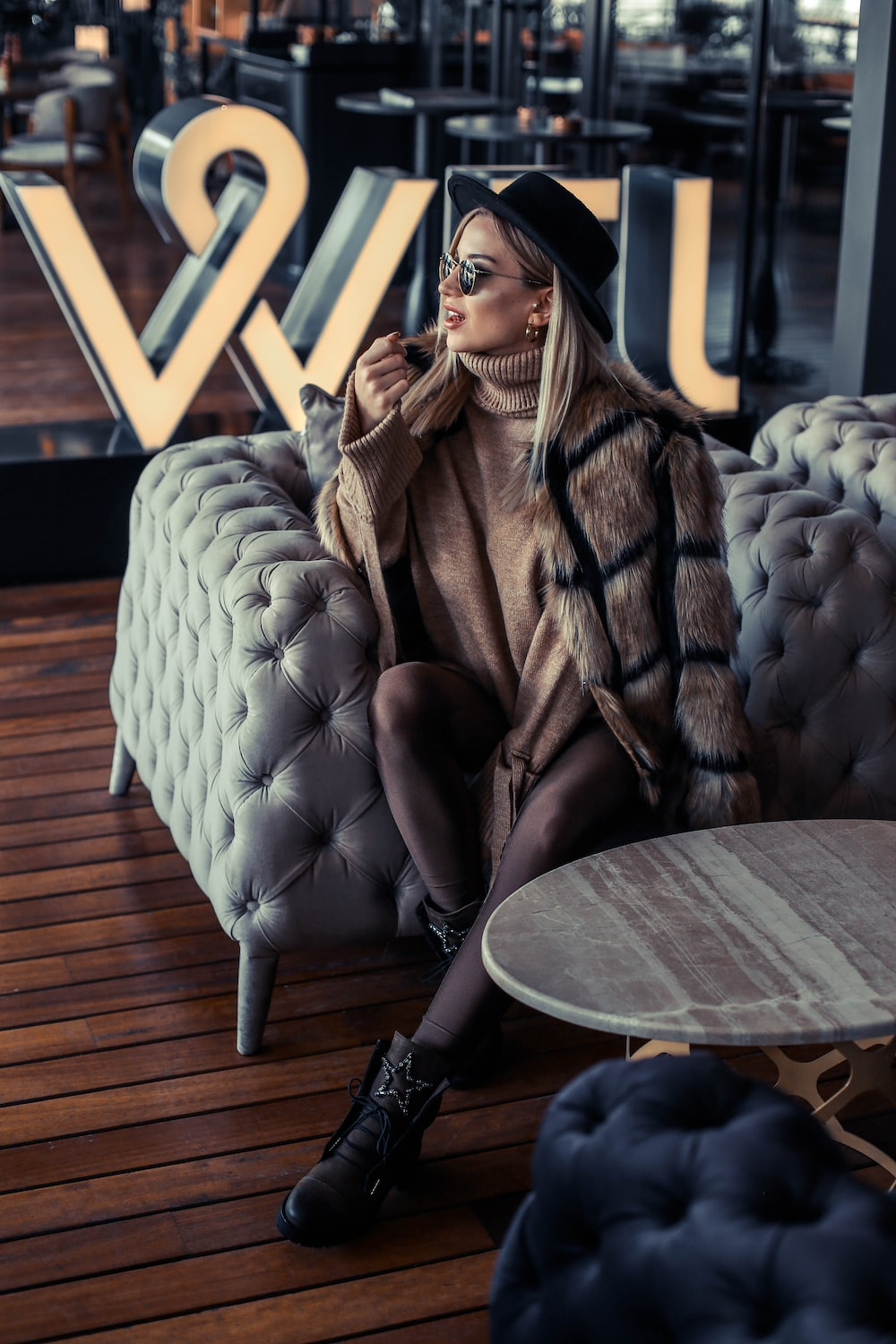 woman sitting on tufted sofa chair wearing fur coat