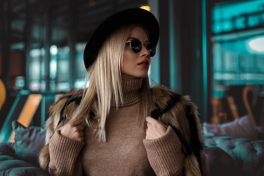 woman wearing brown turtleneck sweater, black hat and black sunglasses