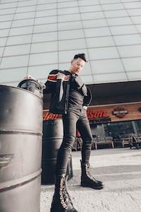 man wearing black leather boots standing near barrel
