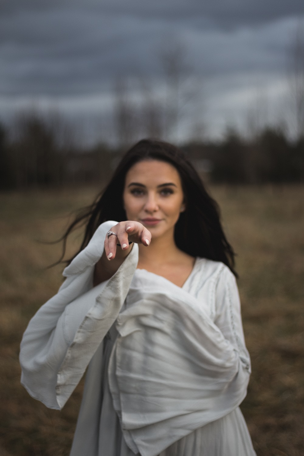 selective focus photography of woman reaching right hand during daytime