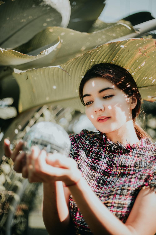 woman holding water globe under banana leaf